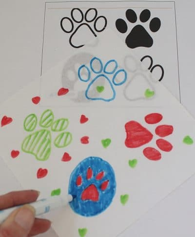Dog paw clipart on a white background. Markers in green, blue and red drew the clipart paws on fabric squares.