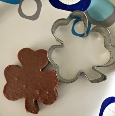 Shamrock cookie cutter and shamrock fudge on a plate.
