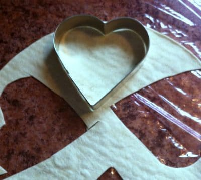 Cutting a heart shaped tortilla with a heart cookie cutter.