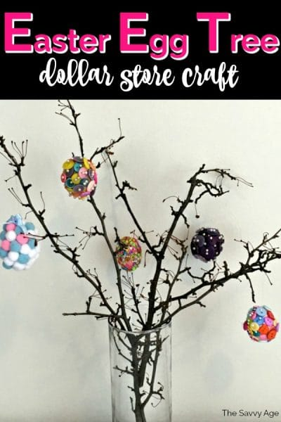 Branches in a clear glass vase decorated with fake colorful Easter eggs.