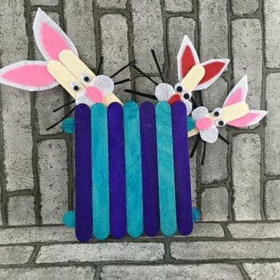 Aqua and purple popsicle stick fence with three popsicle stick bunnies peeking out the top of the fence.