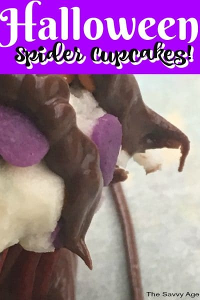 Chocolate spider legs hanging off a cupcake.