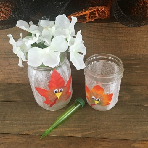 mason jar decorated with a turkey and fresh flowers.