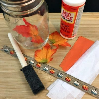 Materials to make mason jar turkey craft: modge podge, jar, brush, tissue paper.