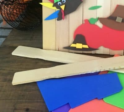 Paint sticks, craft paper next to a paint stick turkey.