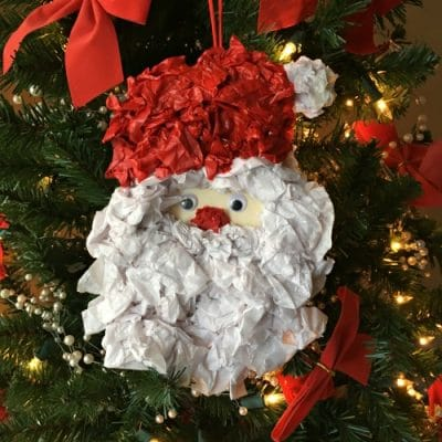Modge podge tissue paper Santa ornament hanging on Christmas tree.