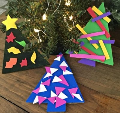 3 painted cardboard tree ornaments decorated with foam paper ornaments.