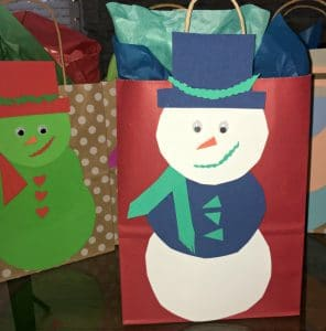 Handmade paper snowman on the outside of a gift bag.