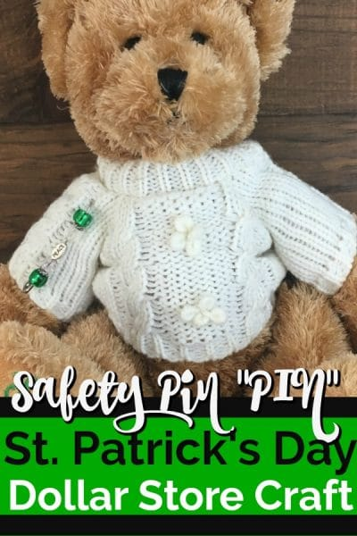 Teddy bear with cream irish cable sweater with a homemade pin made of a safety pin and green beads.