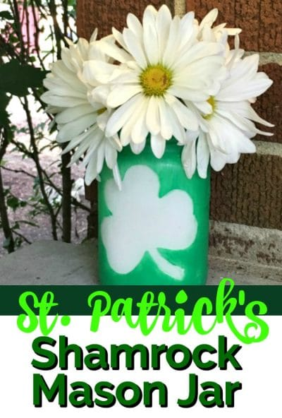 Dreen mason jar with a shamrock on the outside and white daisies.