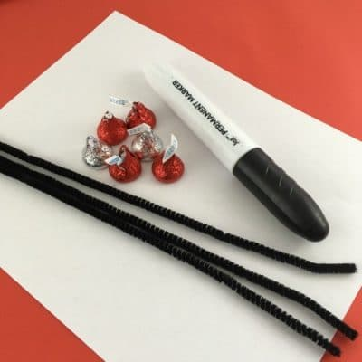 Craft supplies: white paper, black sharpie, black pipe cleaners, hershey kisses red and silver.