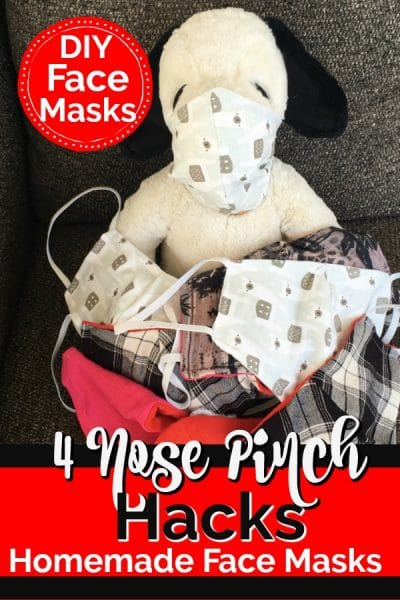 Stuffed animal snoopy wearing a face mask surrounded by homemade face masks on a brown couch.