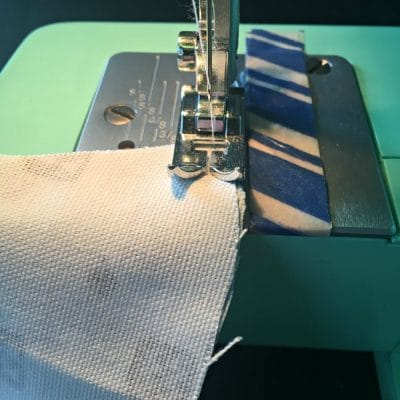 Curved piece of white fabric under a sewing machine needle to be sewn.