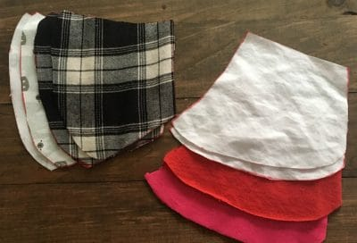 Red, black, white fabric cut into shape of face masks.