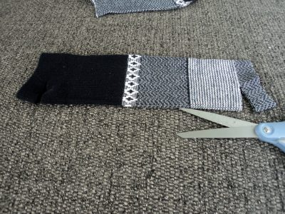 Black and white sock with one cut from edge of sock.