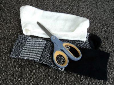 Black sock, white sock and silver scissors