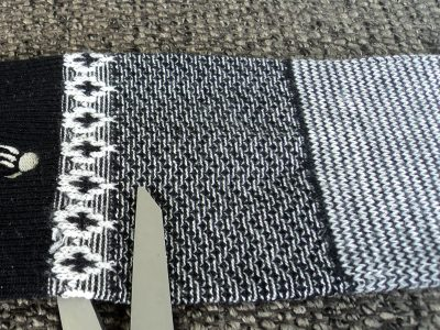 Black and white sock with scissors cutting off top of sock.