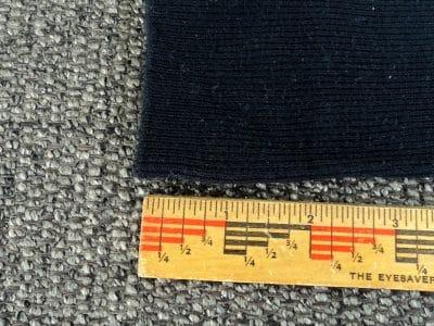 Black sock with ruler on the bottom of sock.