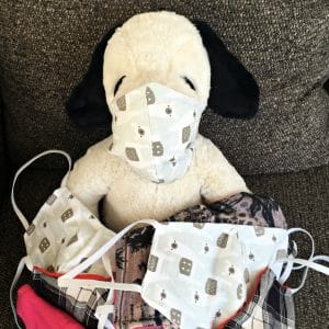 stuffed snoopy with a homemade face mask.