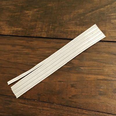Stack of white twist ties on dark brown wood.