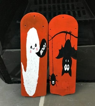 Two orange painted fan blades: one with a white ghost and one with black bats as Halloween door hangers.