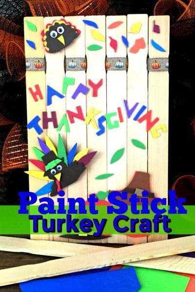 Paint stick made into a fence with turkey and Fall colorful construction paper decorations.