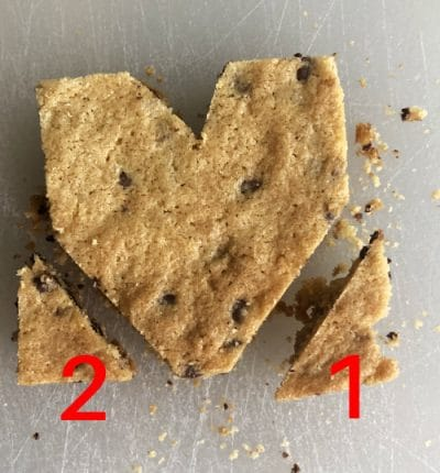 Heart shaped chocolate chip cookie on white background. Number 1 and 2 at each corner to mark cut lines.