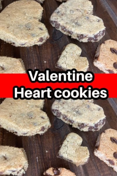 Heart shaped chocolate chip cookies on a brown wood background.